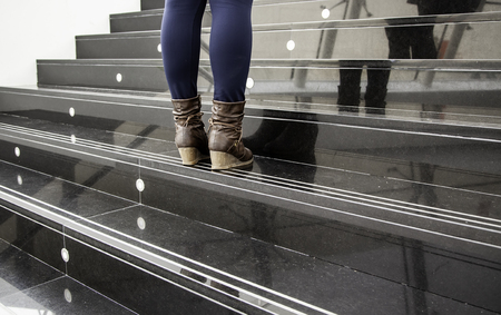 Women's boots on a staircase, fashion detail and present