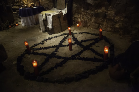 Satanic pentacle with lighted candles, dark magic ritual detail, occultism Reklamní fotografie