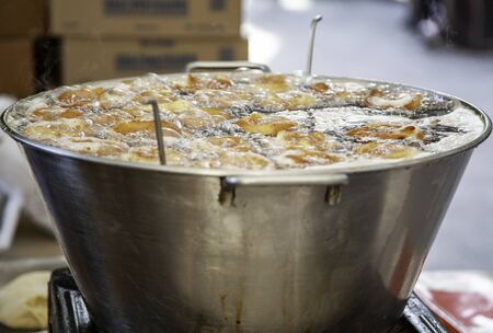 Frying donuts in oil, sweet dessert detail, homemade pastries, sugar-rich food