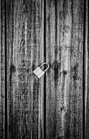 Wooden door locked with a padlock, detail of a textured, protection