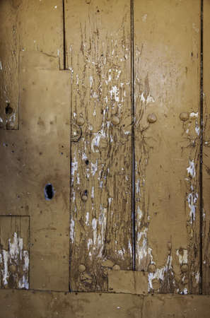 Old brown wooden door with lock, detail of protection, antiquity and abandonment