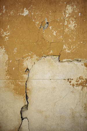 Cement wall with cracks, detail of old facade, abandonment and ruin, destruction