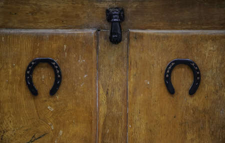 Horseshoe on a door, decoration detail and superstition Фото со стока
