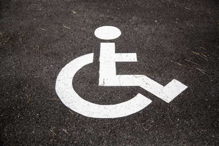 Disabled sign on the asphalt, detail of information and accessibility Фото со стока