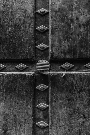 Old black painted wood, detail of decorated door Фото со стока