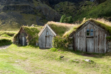 small wooden houses with grass on the roof in iceland