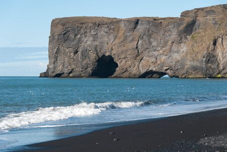 rocky cliff overlooking the sea in Vik in Iceland photo