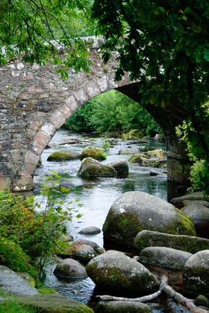 stone bridge with a river and trees on Dartmoor in Cornwall