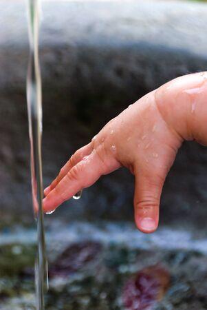sediento: la mano del ni�o s, mientras que tocar la fuente de agua