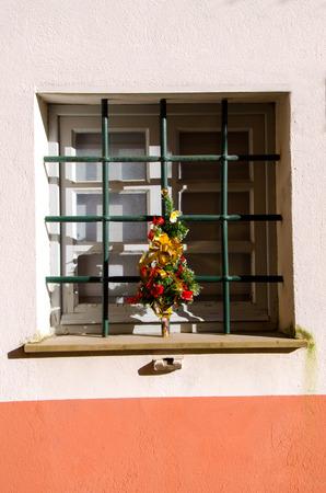 rejas de hierro: ventana con barras de hierro y adornos navideños Foto de archivo