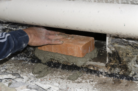 restructuring: positioning a brick with cement at a construction site