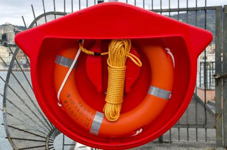 lifesaving: lifesaver orange with yellow tail in the Port of Genoa Stock Photo