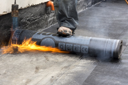 worker burning while the waterproof membrane on a roof