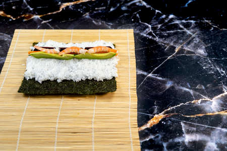 homemade sushi traditional japanese master making healthy maki rolls with prawns cucumber carrot fish