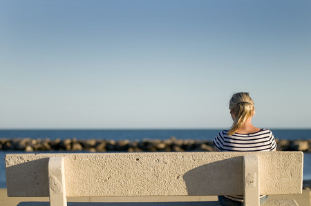solitude: woman looking out to sea Stock Photo