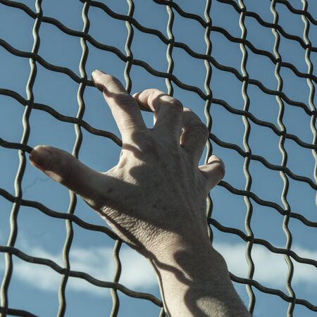 incarcerate: a hand on grate