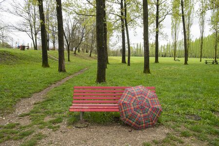 red umbrella: bench with red umbrella in the park Stock Photo