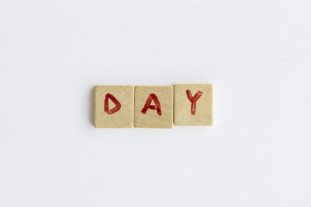 letterpress words: Day word formed with the letters written on pieces of wood square Stock Photo