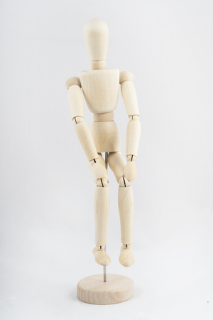 a wooden mannequin in a sitting position