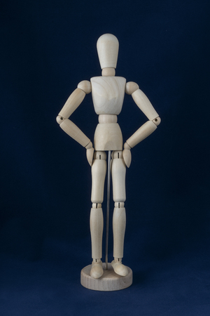 a wooden dummy posing on a blue background Stock Photo