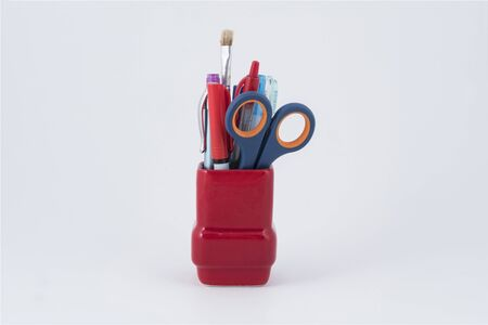 some pens, brush and a pair of scissors in a red pen holder