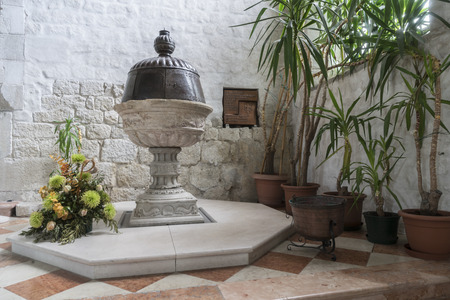 The baptismal font of the sixteenth century in the church of San Andrea in Venzone, Friuli, Italy