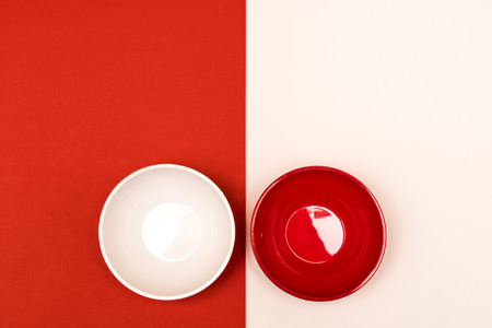 red and white bowls arranged opposite each other on a colored background