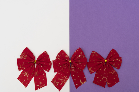 red Christmas bows on a colored background