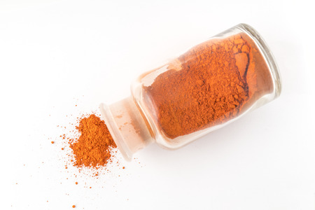 glass flask containing natural orange colored pigment powder