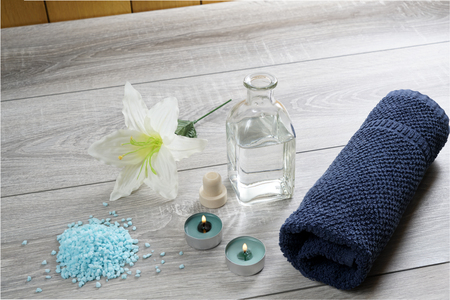 a bottle of massage oil, salts and a towel on the table
