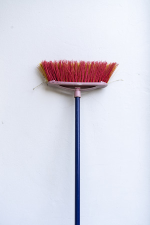 a colored broom leaning against the wall