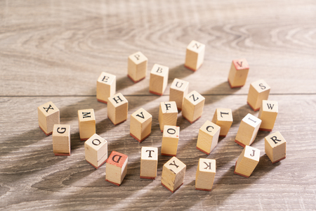 letters printed on wooden cubes scattered on the table 写真素材
