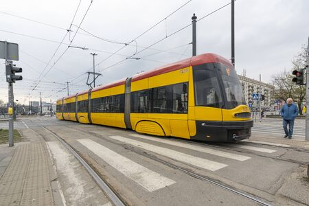 Warsaw, Poland. April 2019.   A yellow tram on the street in the center of the city Redactioneel
