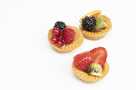 some round pastries with mixed fruit on a white surface