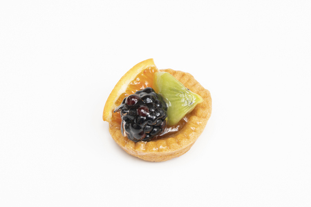 A round pastry with mixed fruit on a white surface
