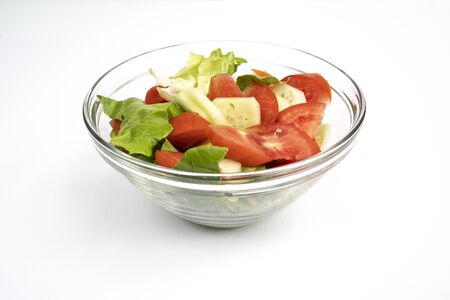 a fresh lettuce, tomato and cucumber salad in a glass bowl