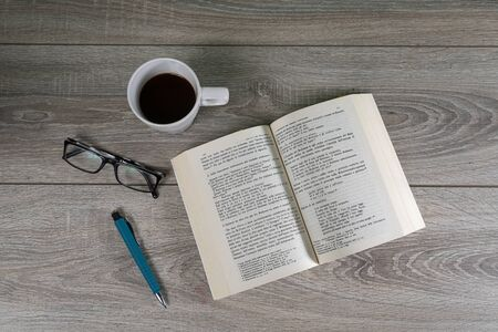 a book on a wooden table with a cup of coffee