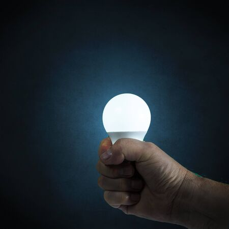a light bulb on in hand with an antique blue background