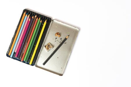 a metal box of colored pencils and a pencil sharpener Stok Fotoğraf
