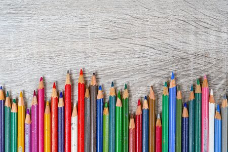 some old colored pencils lined up on a wooden table