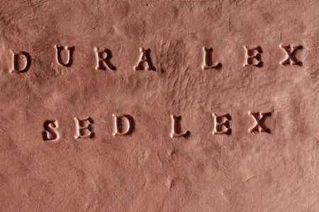 the phrase Dura lex, sed lex written in Latin language on a terracotta tablet