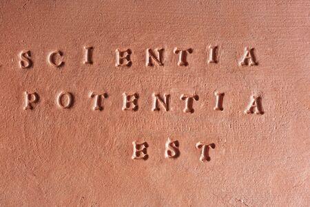 "the phrase  ""Scientia Potentia Est"" written in Latin on a terracotta tablet"