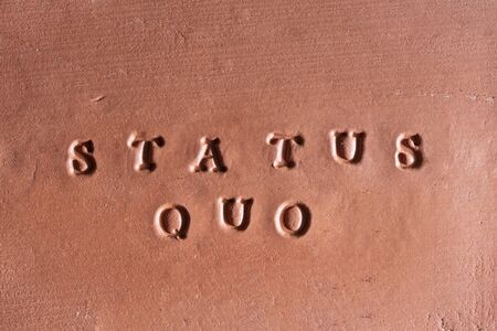 "the phrase  ""Status Quo"" written in Latin on a terracotta tablet"