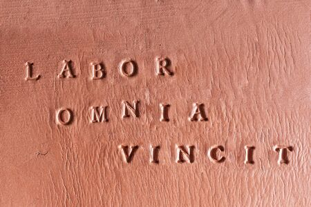 "the phrase  ""Labor Omnia Vincit"" written in Latin on a terracotta tablet"