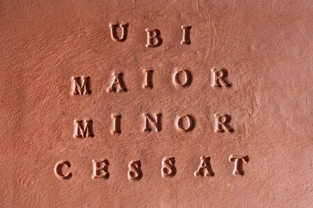 """the phrase  """"Ubi maior, minor cessat� written in Latin on a terracotta tablet"""