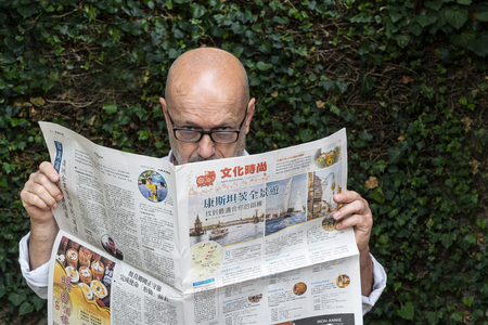 Udine, Italy. July 15 2019.  a western man reading the Chinese Epoch Times newspaper