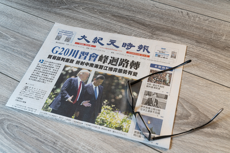 Udine, Italy. July 15, 2019.  The lecture of the Chinese Epoch Times newspaper on a wooden table Editorial
