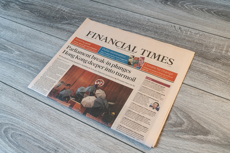 Udine, Italy. July 15, 2019.  The lecture of the  Financial times newspaper on a wooden table