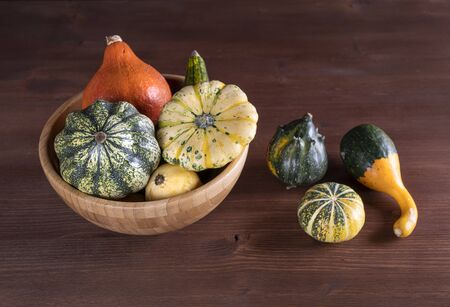 Some small pumpkins on a wooden table in the autumn with some leaves
