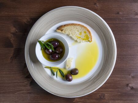 Olive oil and olives on a plate on wooden surface with some Olive branches
